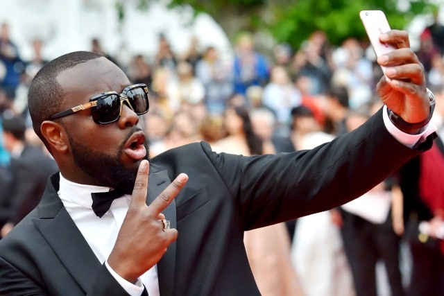"""Congolese-born French rapper Maitre Gims takes photos as he arrives on May 14, 2016 for the screening of the film """"The BFG"""" at the 69th Cannes Film Festival in Cannes, southern France. / AFP PHOTO / LOIC VENANCE"""