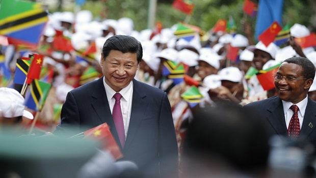 China's President Xi Jinping (L) and his Tanzanian counterpart Jakaya Kikwete (R) walk through women waving China and Tanzania national flags at the State House in Dar es Salaam, March 24, 2013. Xi faces growing calls from policymakers and economists in Africa for a more balanced trade relationship between the continent and China as he arrives in Tanzania at the beginning of an African tour on Sunday. REUTERS/Thomas Mukoya (TANZANIA - Tags: POLITICS BUSINESS)