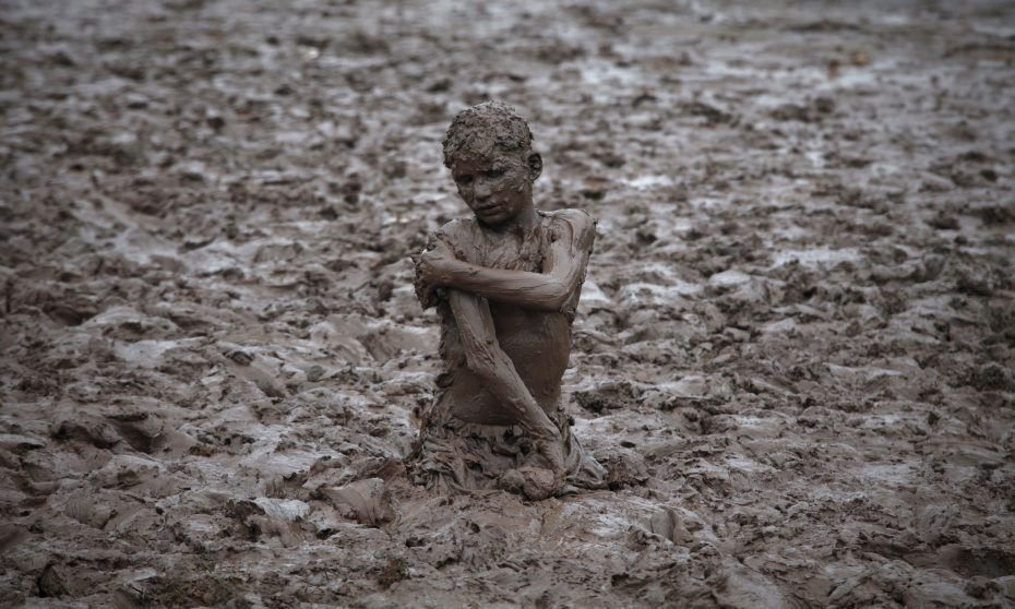 A boy plays in the mud near the Ravi river after a downpour on the outskirts of Lahore August 24, 2011. REUTERS/Mohsin Raza (PAKISTAN - Tags: SOCIETY ENVIRONMENT IMAGES OF THE DAY)