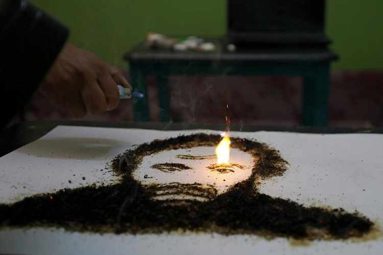 A portrait of the Egyptian actor Adel Imam made of tobacco by artist Abdelrahman al-Habrouk, burns in Alexanria, Egypt August 10, 2017. Picture taken August 10, 2017. REUTERS/Mohamed Abd El Ghany - RTS1BM7U